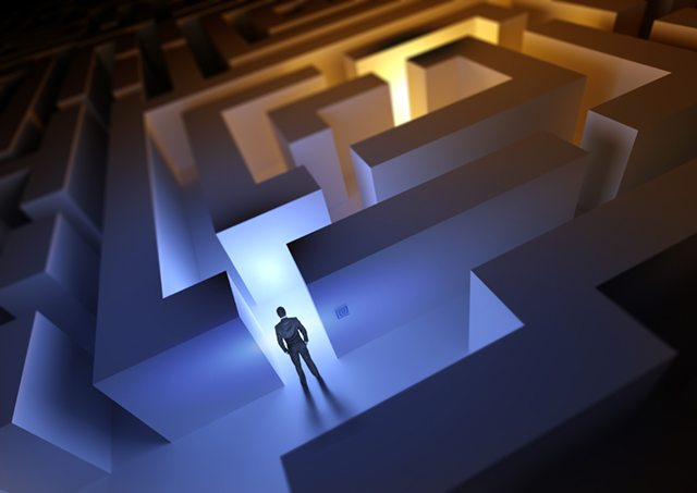 A businessman with a challenge / maze ahead of him.