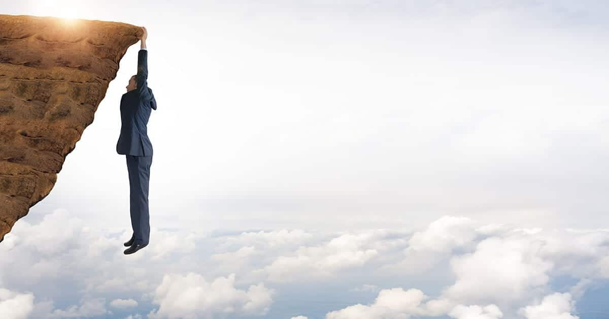 resilient person hanging from a cliff above blue clouds